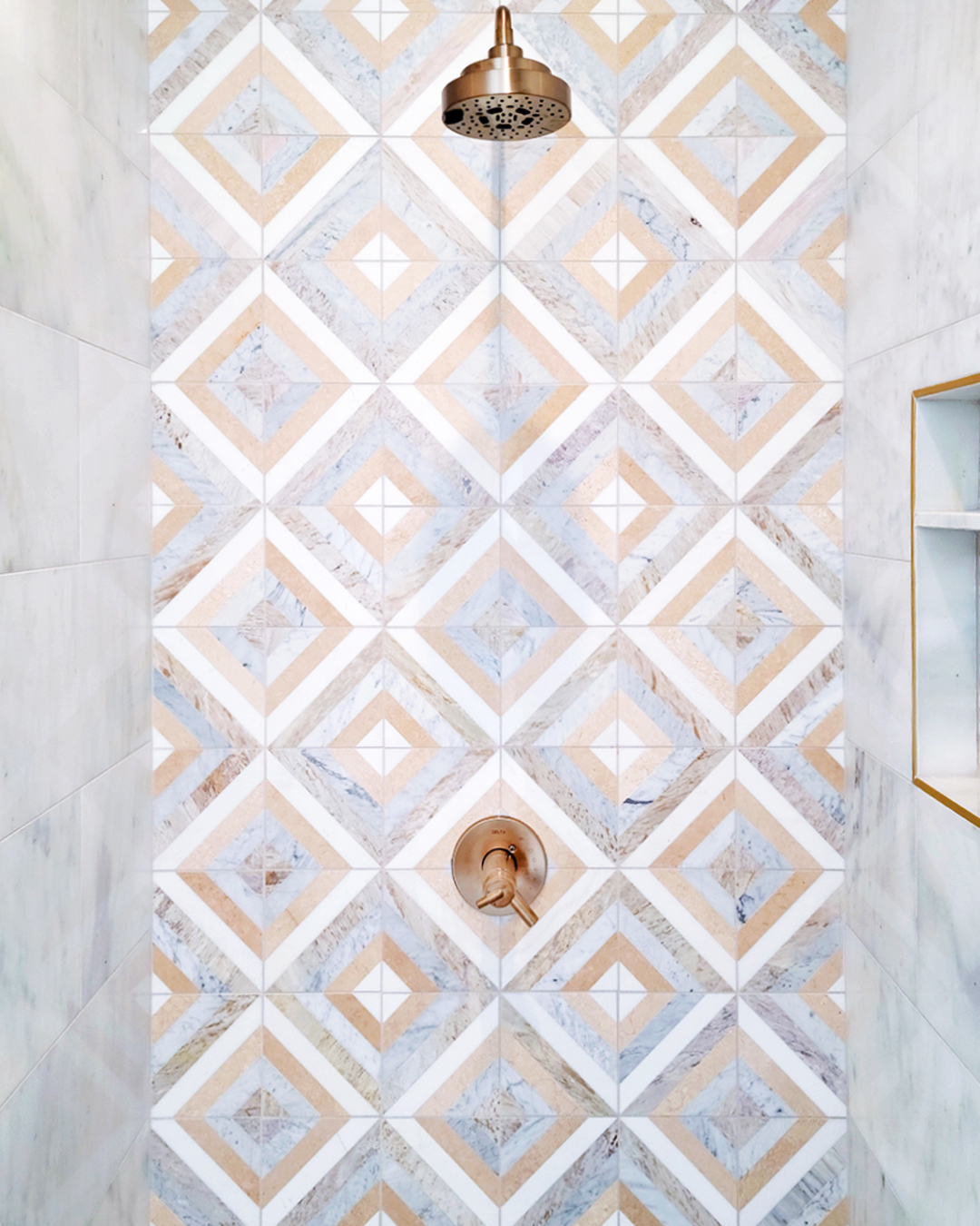 shower wall with brass fixtures and geometric tiles